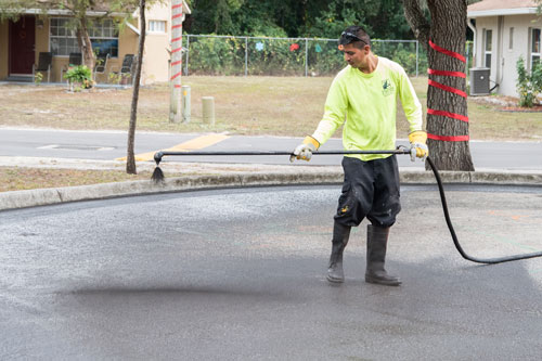 Sealcoating Spraying on Asphalt Driveyway - Collier Paving and Concrete